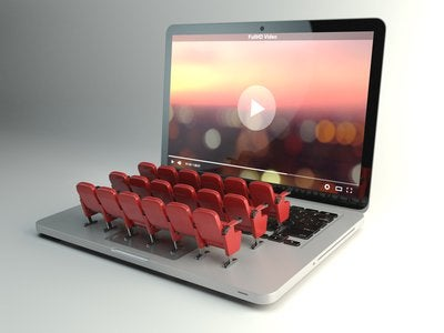 Theater seats arranged on a laptop keyboard facing the screen that is streaming a video.
