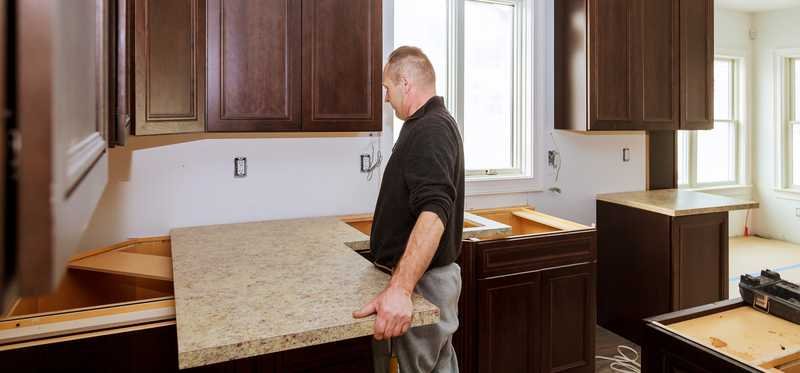 Man installing a new counter top in a kitchen.