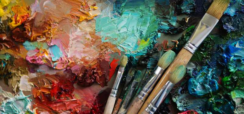 A canvas with brightly colored paints and brushes.