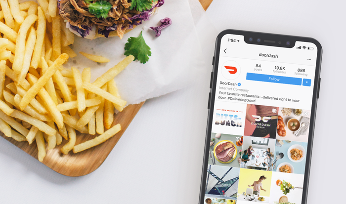 Phone with DoorDash app open sitting next to meal of fries and sandwich