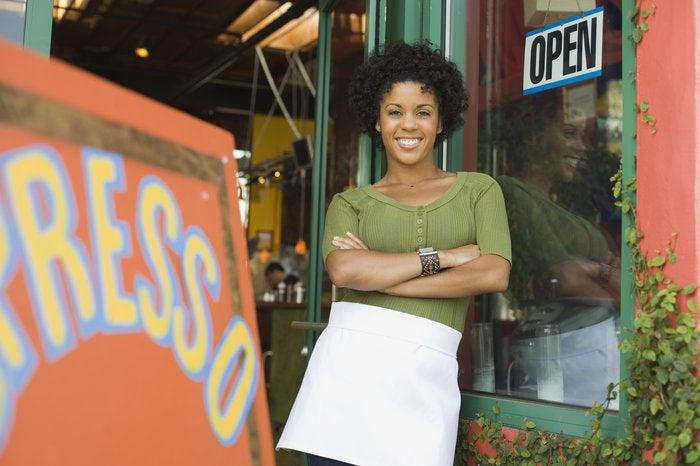 Smiling woman wearing apron standing outside coffee shop with her arms folded