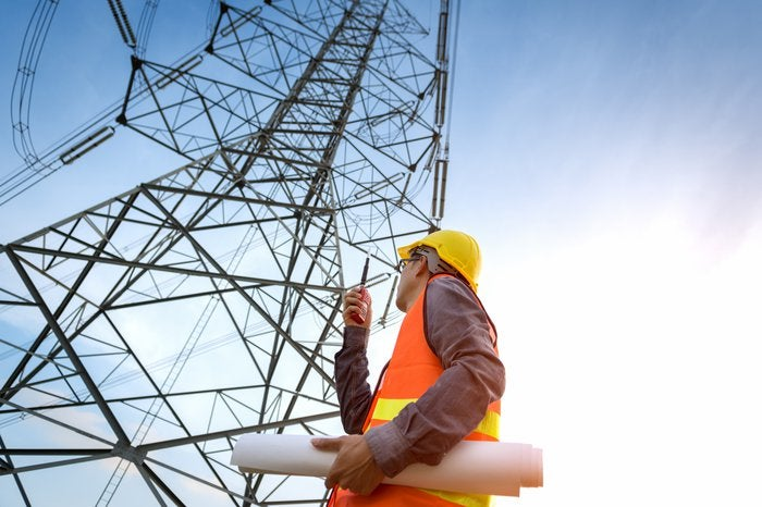 A worker standing at the bottom of a telecom tower.