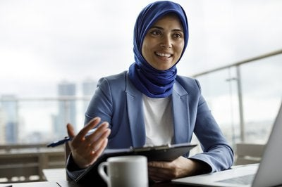 woman in business suit in front of computer while speaking