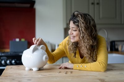 Woman with long curly hair puts coins in piggy bank