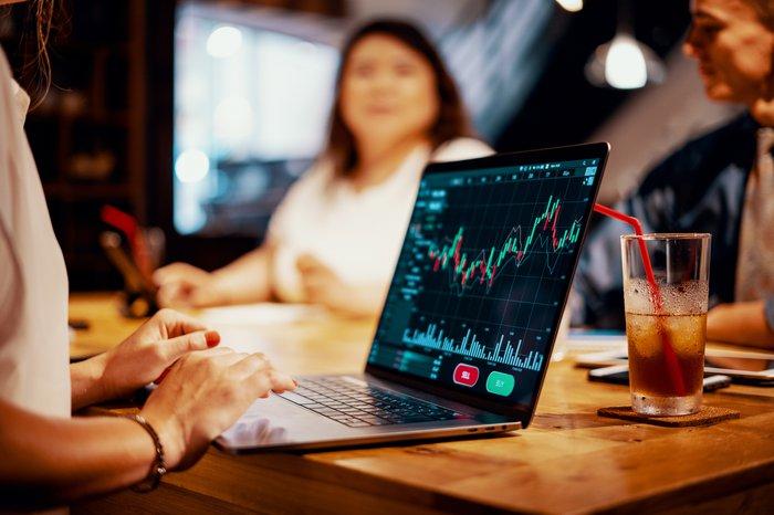 Femme assise à table avec d'autres et regardant le graphique boursier sur ordinateur portable