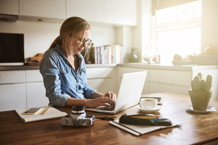 Woman typing on laptop on kitchen counter