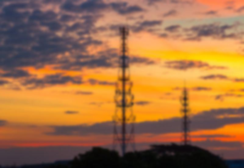 Cell towers with an orange sky behind them