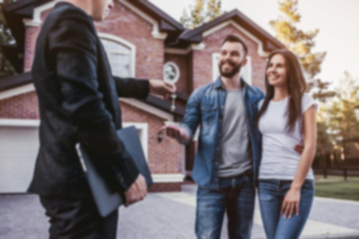 Couple being handed keys in front of brick house