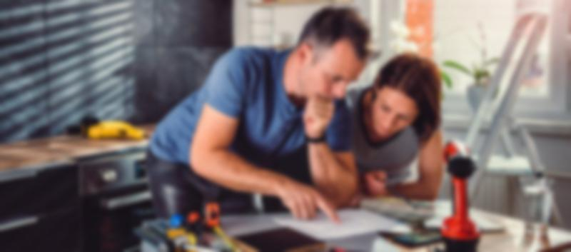 couple discussing construction with tools and paint samples