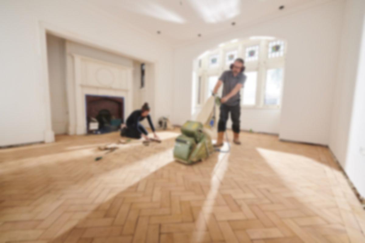 couple refinishing a floor