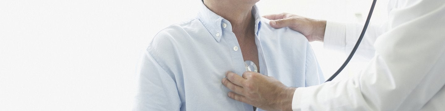 Doctor holding stethoscope to male patient's chest