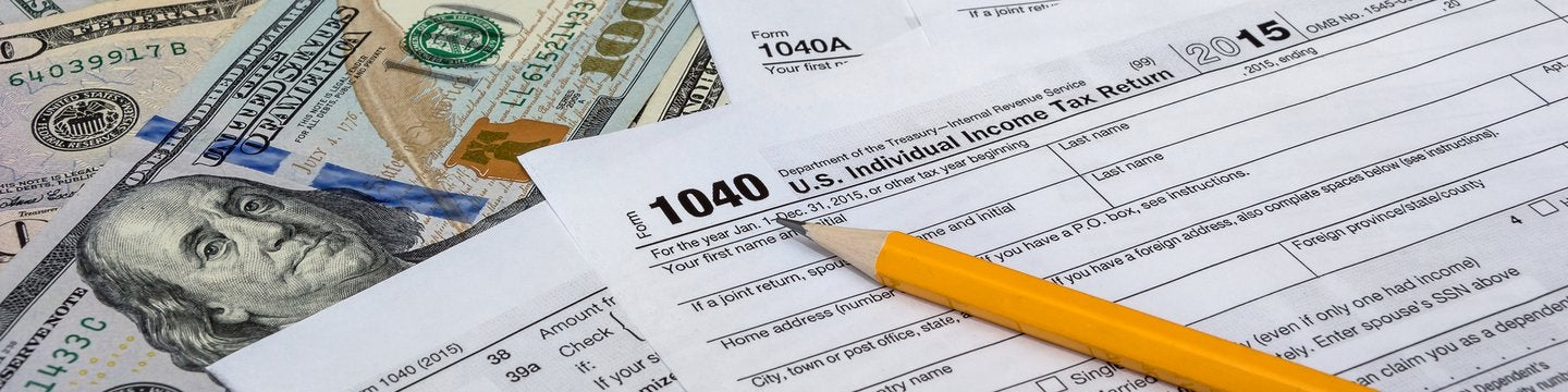 1040 tax form and dollar bills