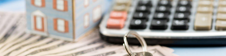 calculator, dollar bills, and silver keys