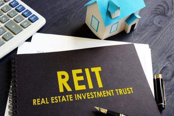 REIT real estate investment trust black booklet on desk