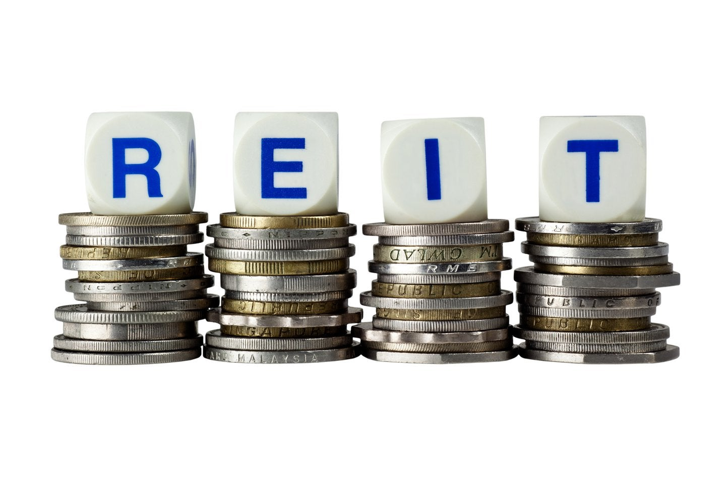 REIT on white dice on top of stacks of coins