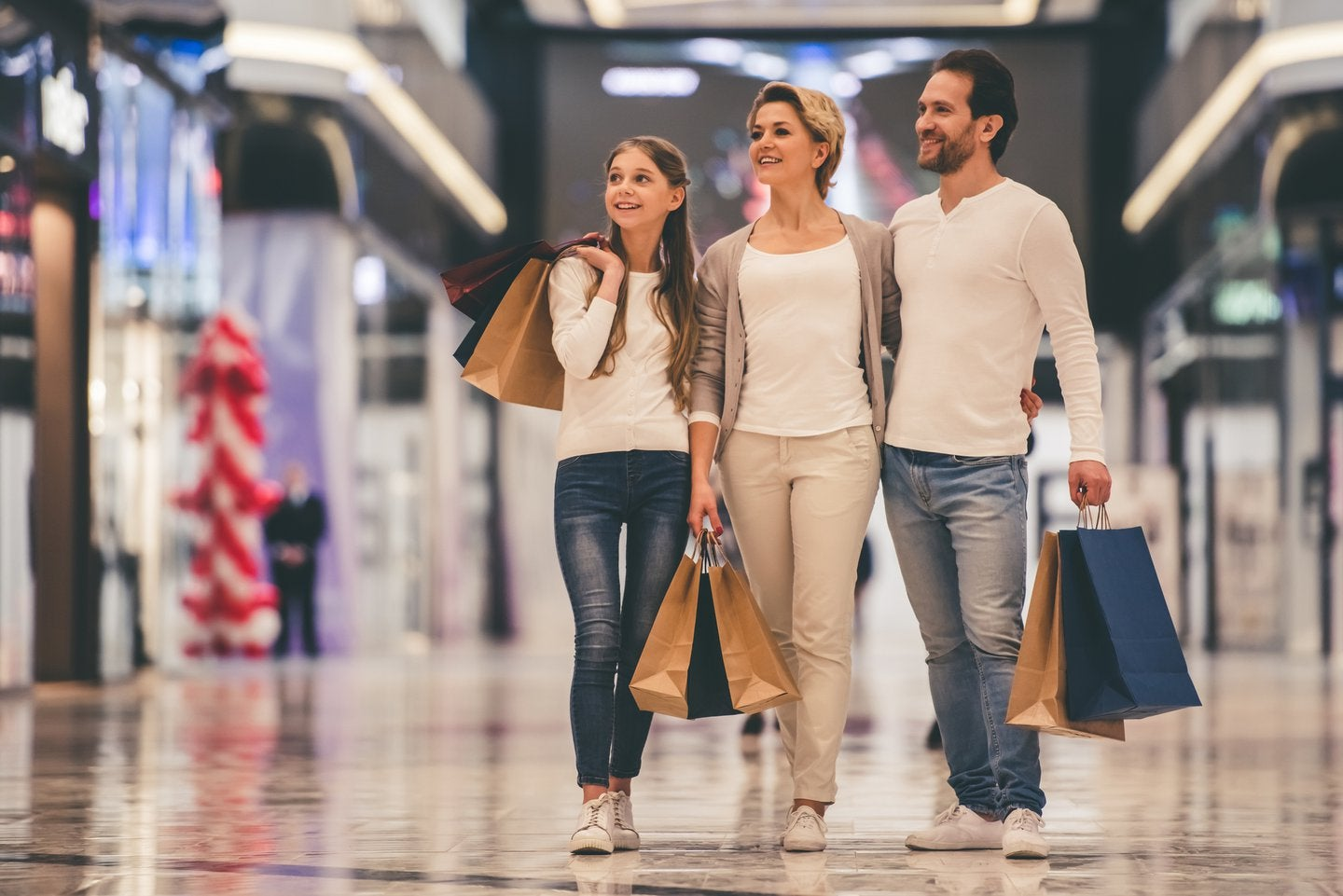 three people happily shopping at a shopping mall