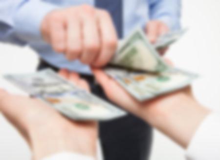 close up of man handing several 100 dollar bills to someone