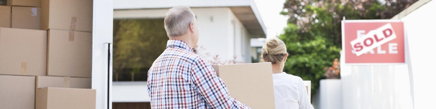 Older couple moving boxes from truck
