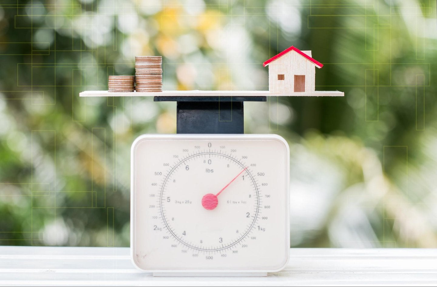 Coins and a house model on a scale