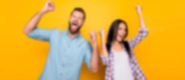 Happy couple against yellow background