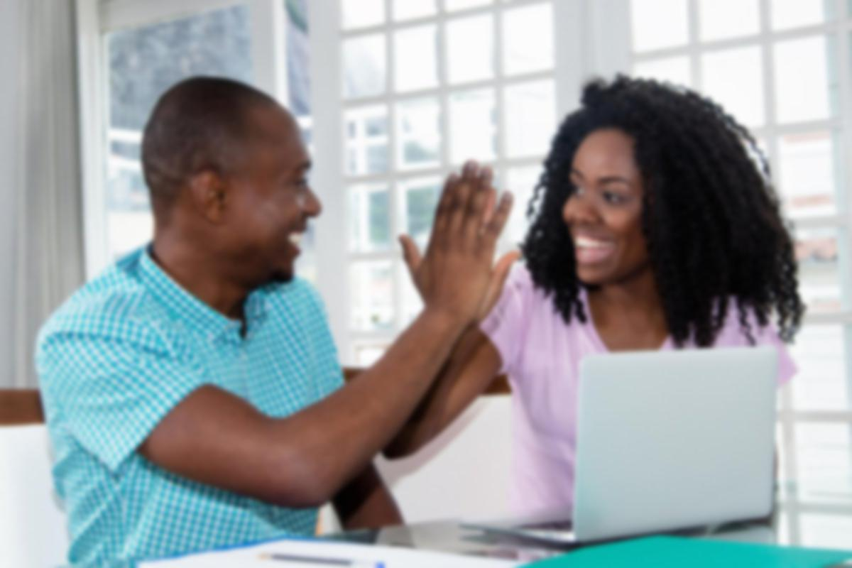 Couple high-fiving next to a computer