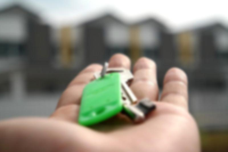 hand with keys in front of building