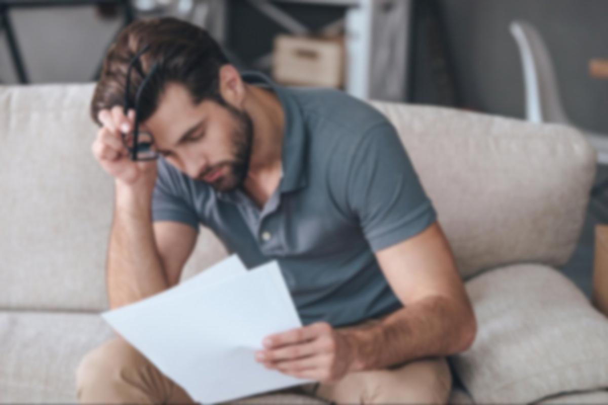 Man looking at documents with glasses off