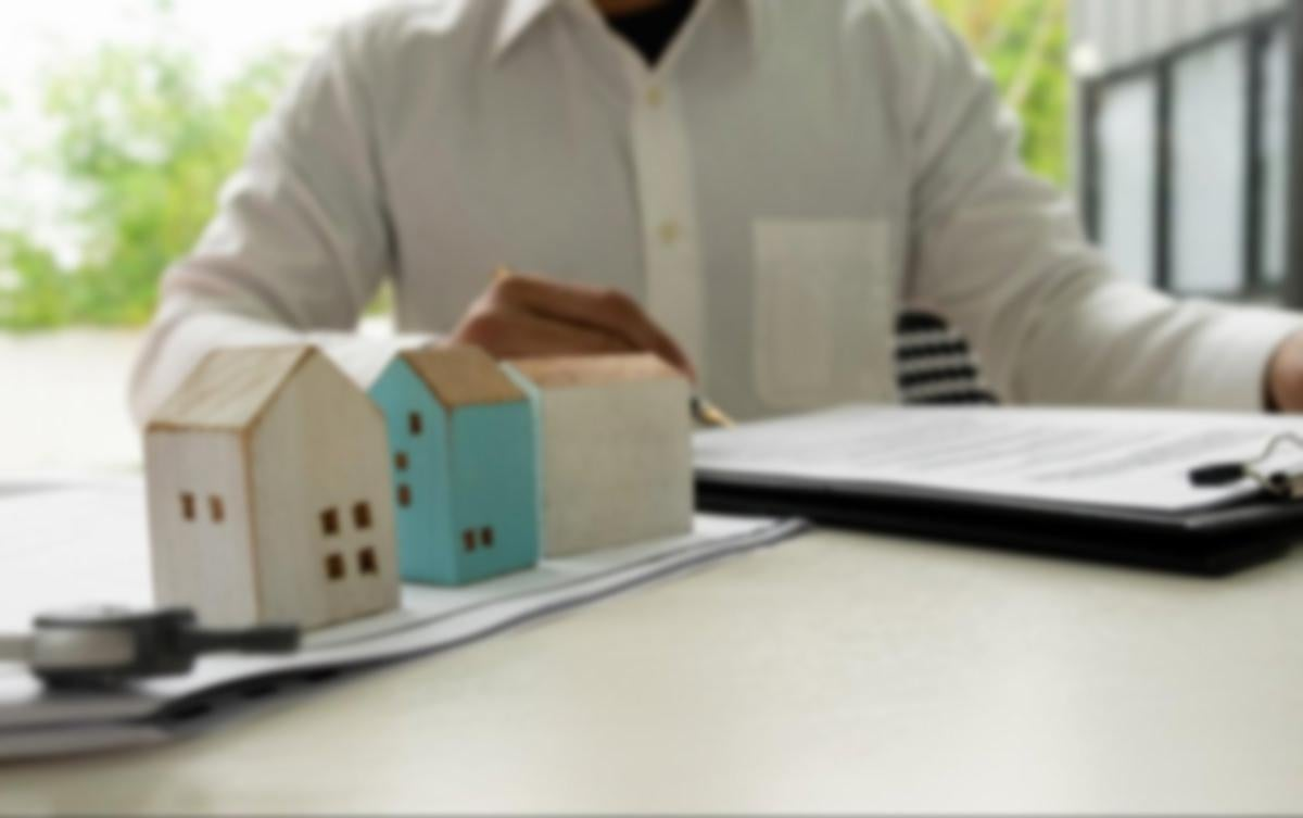 Person calculating finances with a house model