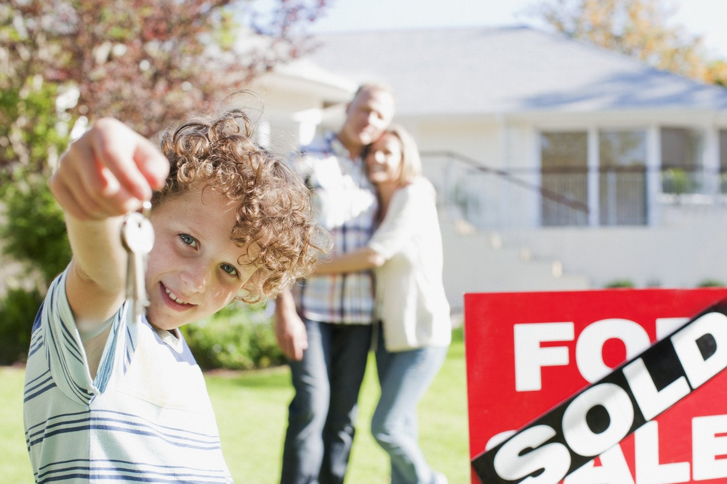Kid with keys in front of house with sold sign and parents