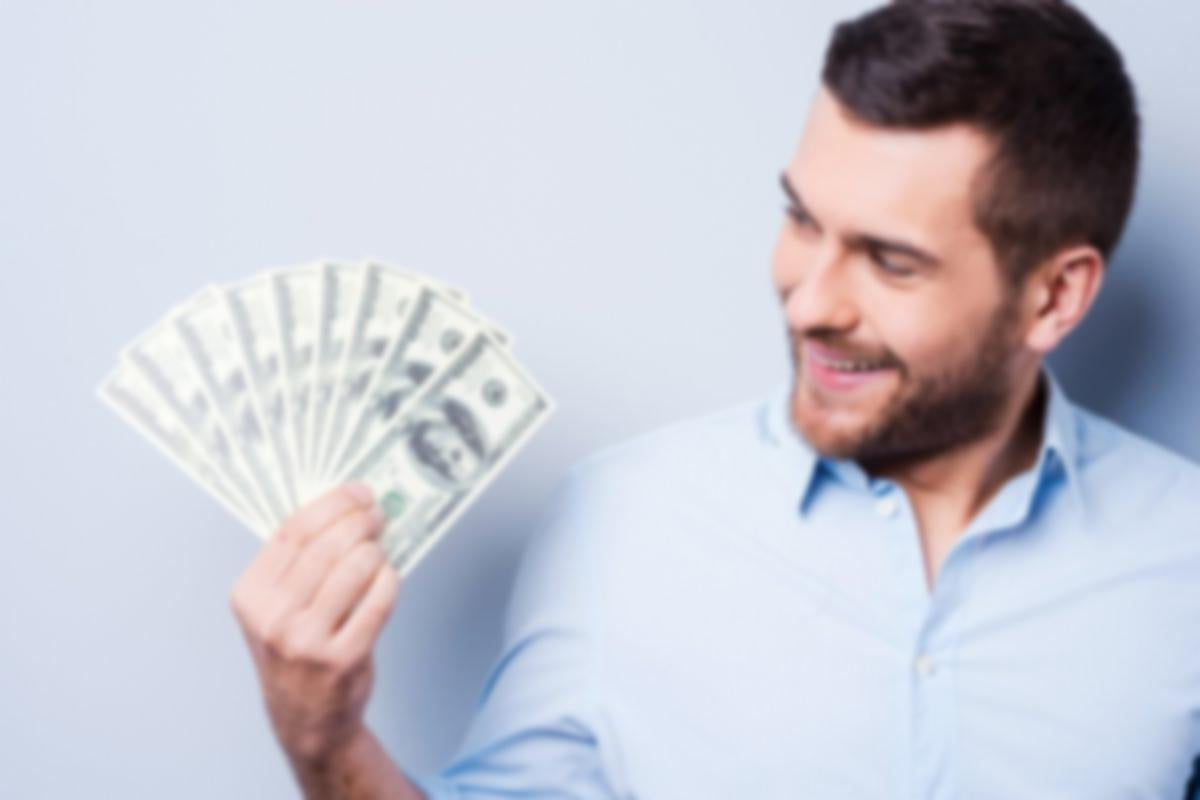 Man smiling at a stack of $100 bills