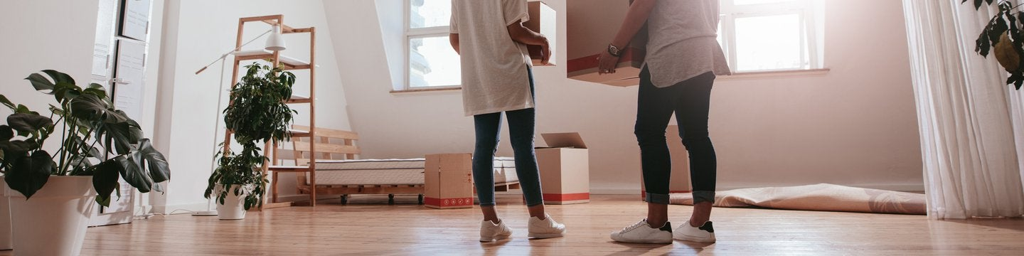 Young man and woman holding boxes and moving in new house.