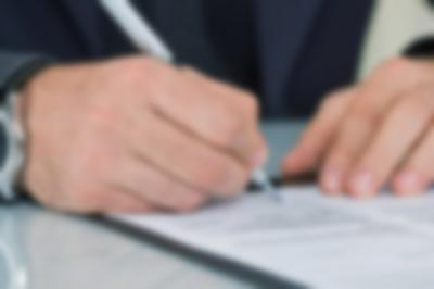person in as suit signing in a contract