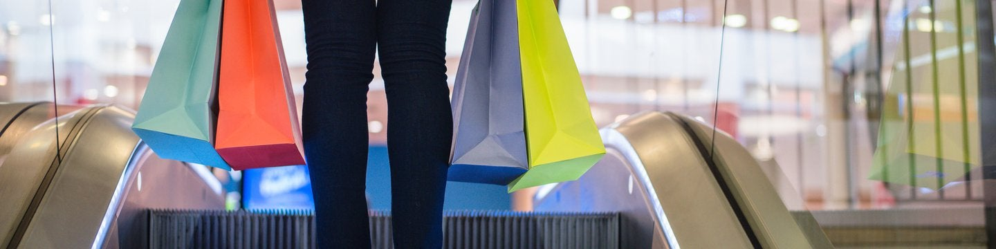 Person on escalator carrying shopping bags