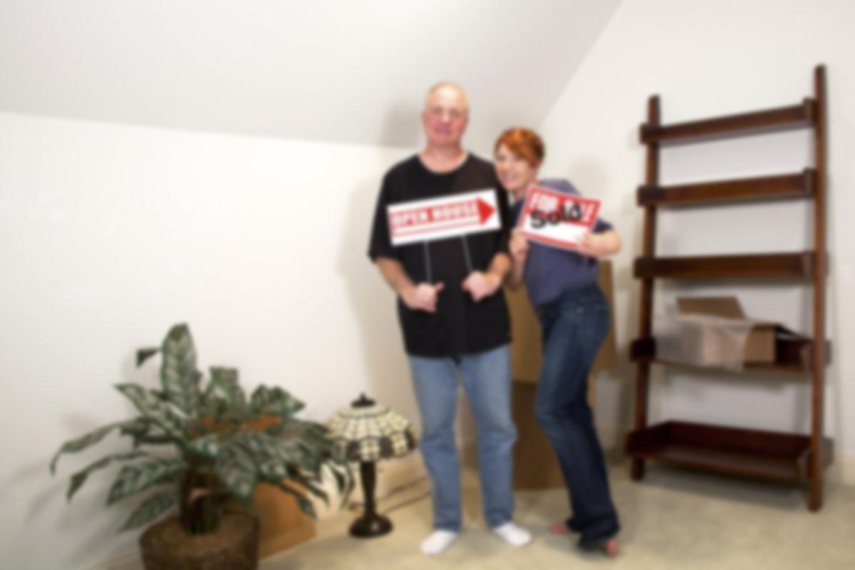 couple with sold house signs