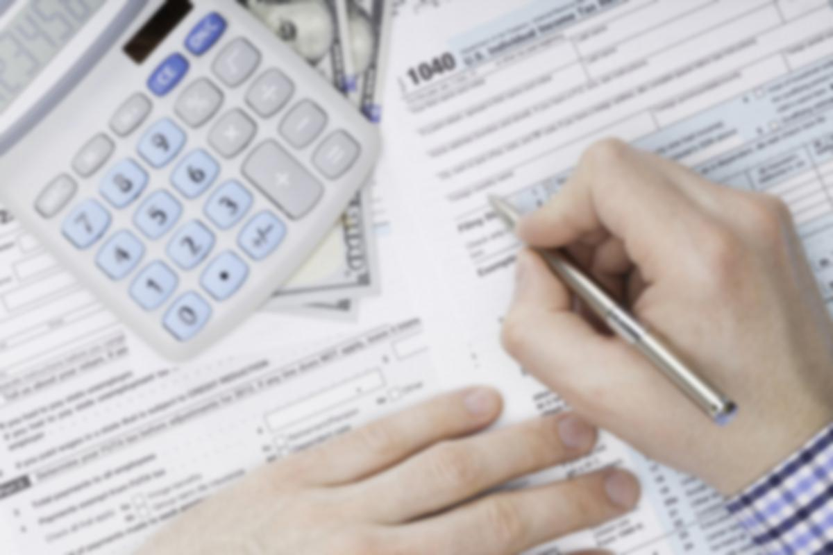 Individual Using Calculator for Personal Taxes