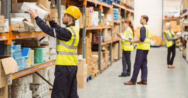 A group of warehouse workers pick items off the shelves to pack for fulfillment.
