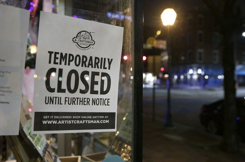 A sign in an art shop window advises customers that the store is temporarily closed, and that customers can shop for delivery online.