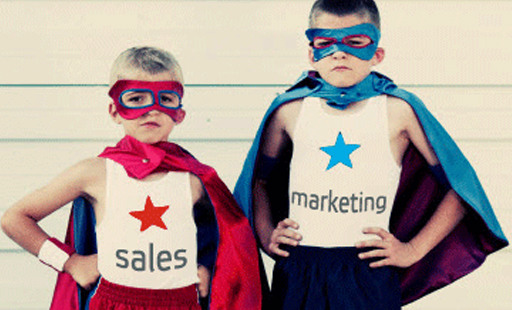 Two children dressed up in superhero costumes labeled sales and marketing