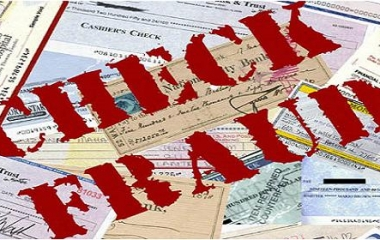 """The words """"CHECK FRAUD"""" in red letters stamped on top of a pile of checks."""
