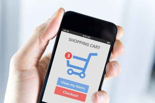 A hand holding a smartphone that show's a shopping cart.