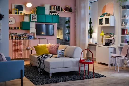 An IKEA living room setup, with pink walls and a cream sofa.