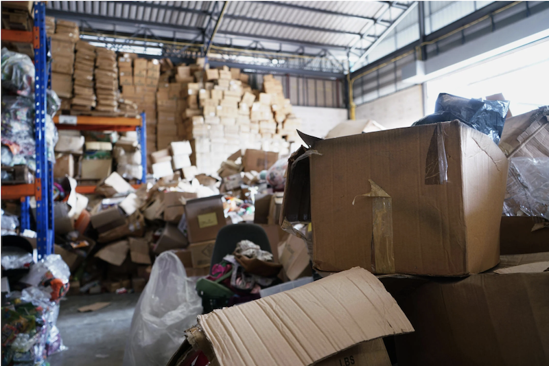 A dirty and disorganized warehouse with open and tipped over boxes stacked everywhere.