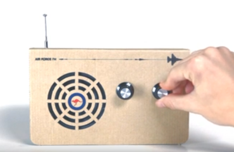 Image of an Air Force FM radio with a hand adjusting the sound.