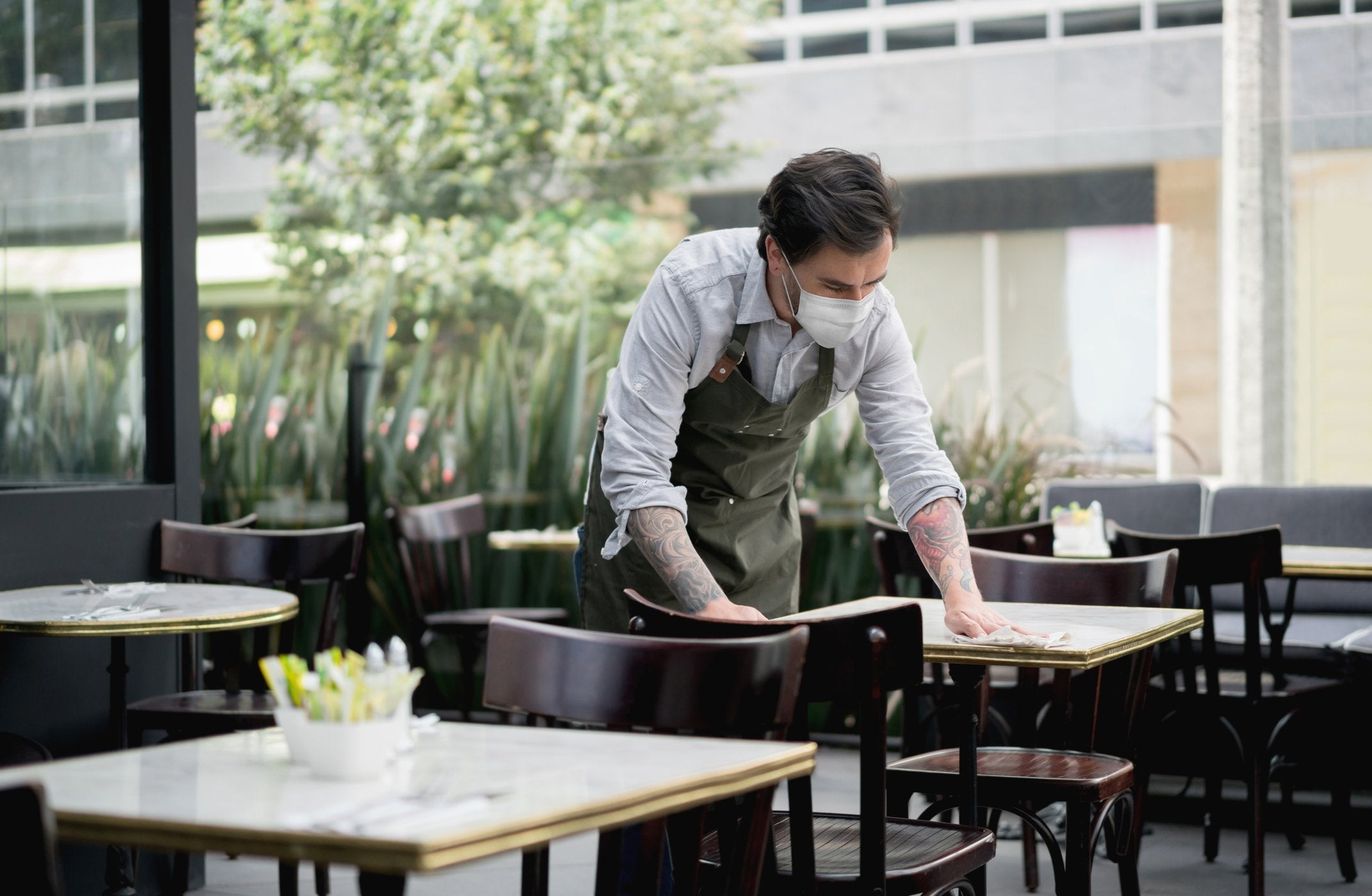 A man in a mask wipes a restaurant table with a cloth.