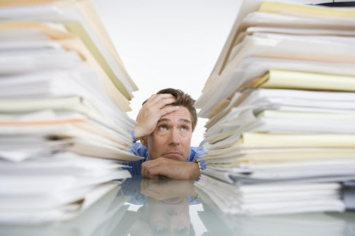 Man looking up at two piles of folders.