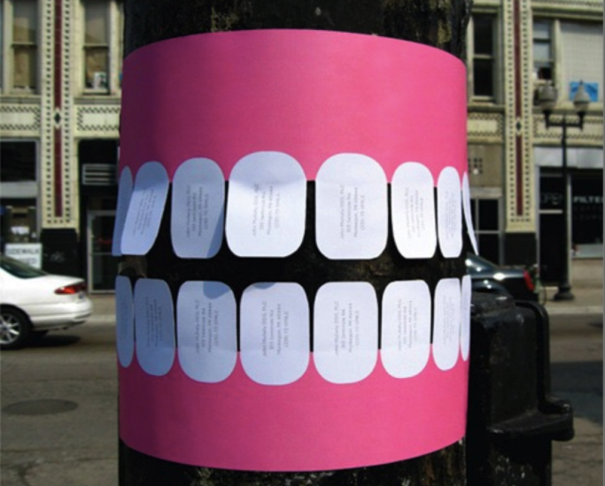 Teeth shaped poster wrapped around a pole.