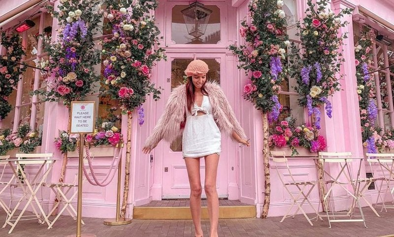 Woman standing outside painted pink cupcake store covered with flowers.
