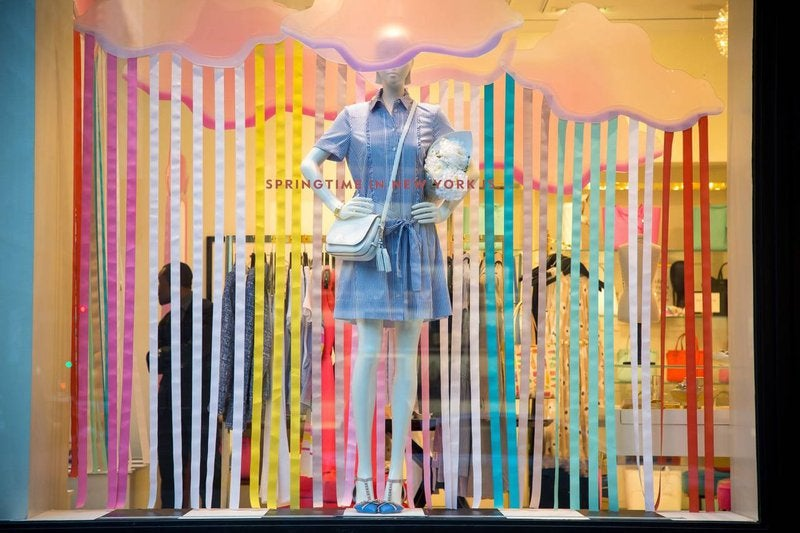 Mannequin standing against multicolored strips of paper and pink clouds in a store window.
