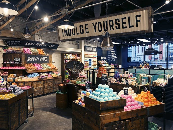 """Image of the inside of a Lush store, showing product displays of bath bombs and a sign reading """"indulge yourself."""""""