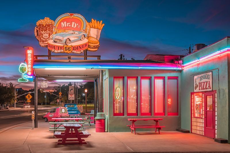 A red and turquoise diner has red picnic tables outside the establishment.